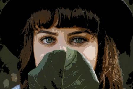 Kappale kauneinta Suomea. Kaunis tyttö, siniset silmät, salaperäinen katse. Kurkistaa vihreän lehden takaa.