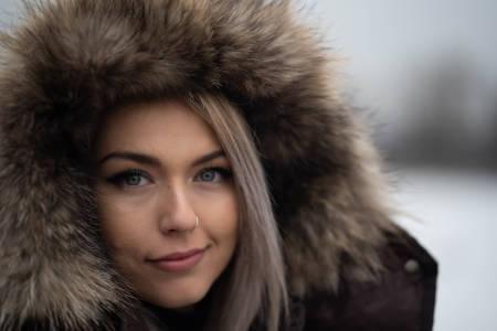 Smiling girl face closeup. Winter. Warm parka.